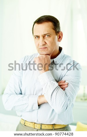 Portrait of mature man with crossed arms touching his chin - stock photo