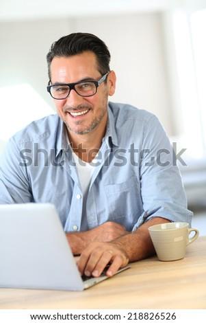 Portrait of mature man working on laptop - stock photo