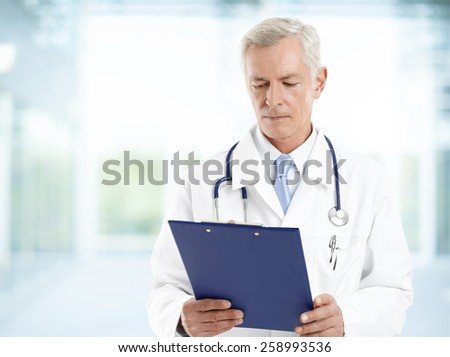 Portrait of mature medical doctor holding clipboard in his hands and standing at private clinic.