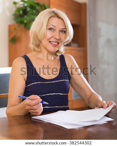 Portrait of mature smiling businesswoman with financial documents at home