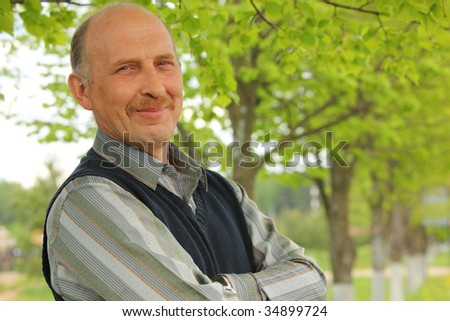 portrait of mature smiling man with crossed hands outdoor - stock photo