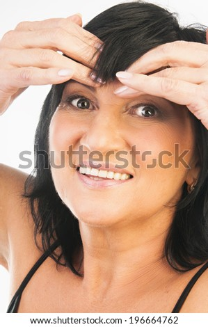 Portrait of mature woman beauty massaging her forehead isolated on white background