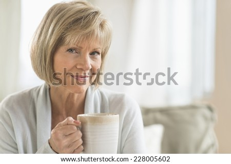 Portrait of mature woman holding coffee mug at home - stock photo