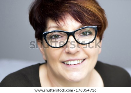 portrait of mature woman in black glasses - stock photo