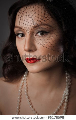 Portrait of Mature woman in pearl necklace and a black veil - stock photo
