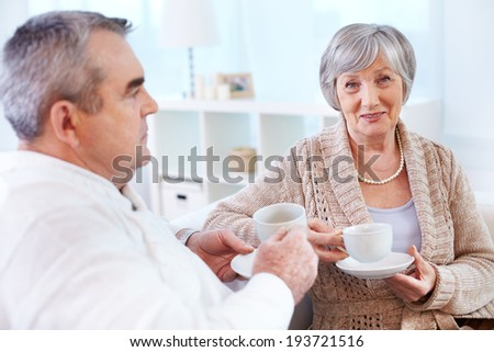 Portrait of mature woman looking at camera while drinking tea and interacting with her husband - stock photo