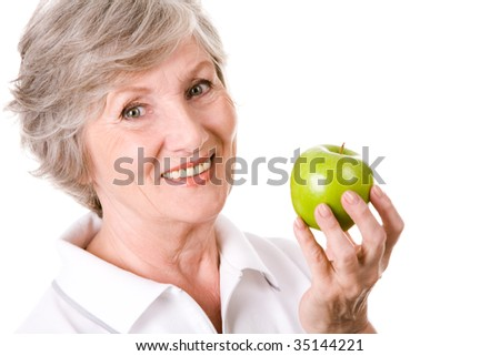 Portrait of mature woman smiling with green apple in hand - stock photo