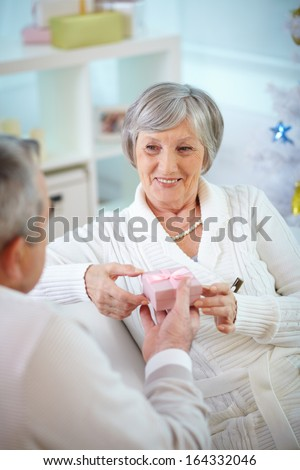 Portrait of mature woman taking small giftbox given by her husband - stock photo