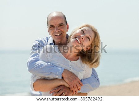 Portrait of mature woman with elderly man against sea in background