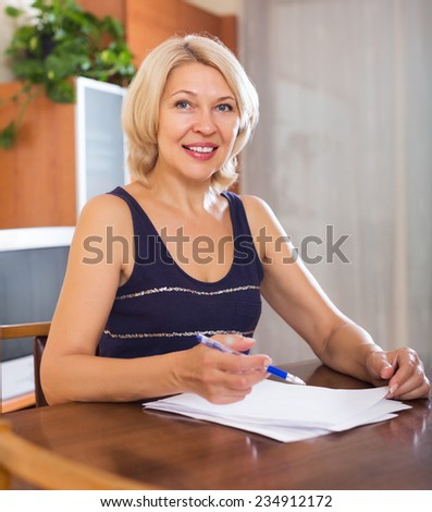 Portrait of mature woman with financial documents at home