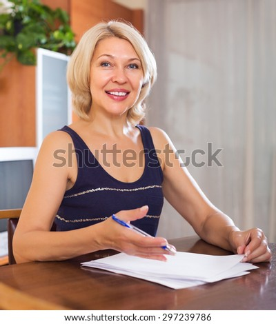 Portrait of mature woman with financial documents in office interior