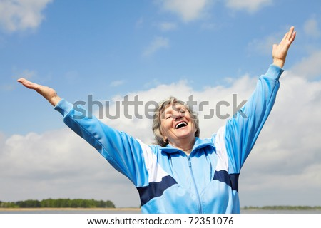 Portrait of mature woman with her arms raised outside - stock photo