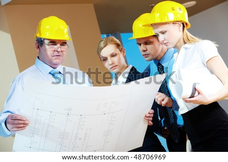 Portrait of mature worker holding a project with three colleagues near by - stock photo