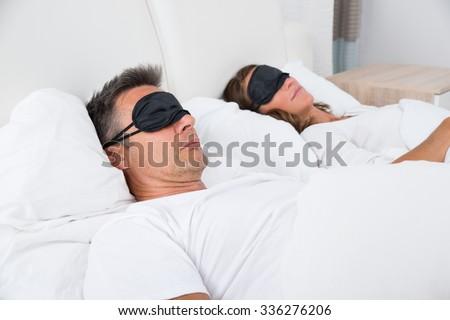 Portrait Of Matured Couple Sleeping Comfortably On Bed Using Eye Mask - stock photo