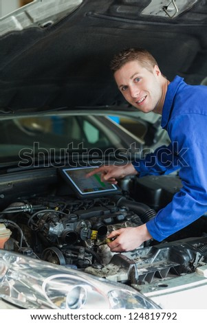 Portrait of mechanic by car using tablet computer - stock photo