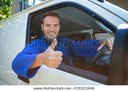 Portrait of mechanic sitting in his car making thumbs up sign - stock photo