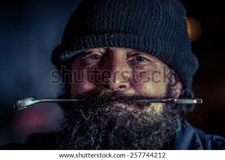 Portrait of mechanic with beard holding steel wrench in mouth - stock photo