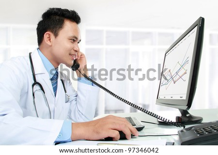 portrait of medical doctor working with his computer - stock photo
