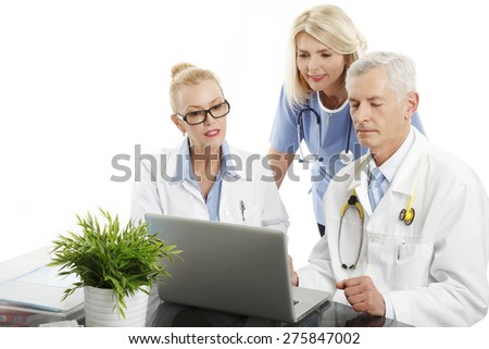 Portrait of medical team sitting at desk in front of laptop and consulting. Doctors and nurse analyzing medical test. Isolated on white background.  - stock photo