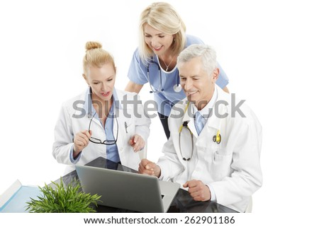 Portrait of medical team sitting in front of computer and consulting. Isolated on white background.  - stock photo