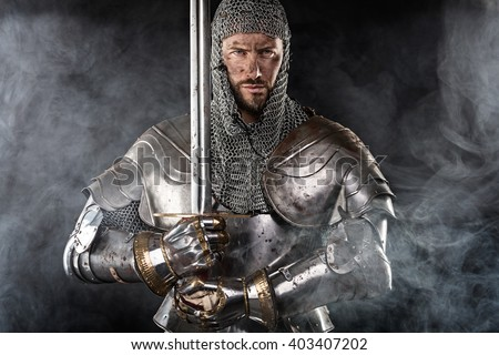 Portrait of Medieval Dirty Face Warrior with chain mail armour and red cross on sword. Cloud smoke on Dark Background - stock photo