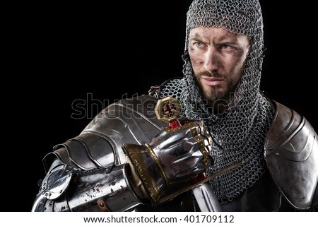 Portrait of Medieval Dirty Face Warrior with chain mail armour and red cross on sword. Dark Background - stock photo