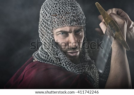 Portrait of Medieval Dirty Face Warrior with chain mail armour and sword. Smoke Cloud on Dark Background - stock photo