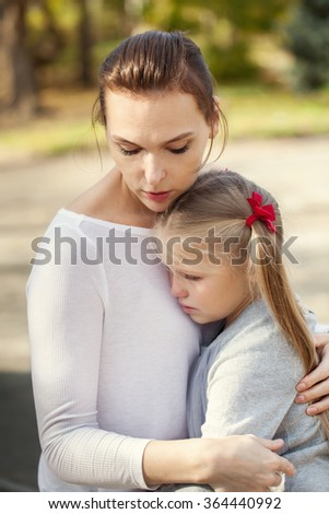 Portrait of melancholy mother and daughter outdoor. - stock photo