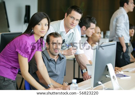 Portrait of men and a woman in the office at a computer - stock photo