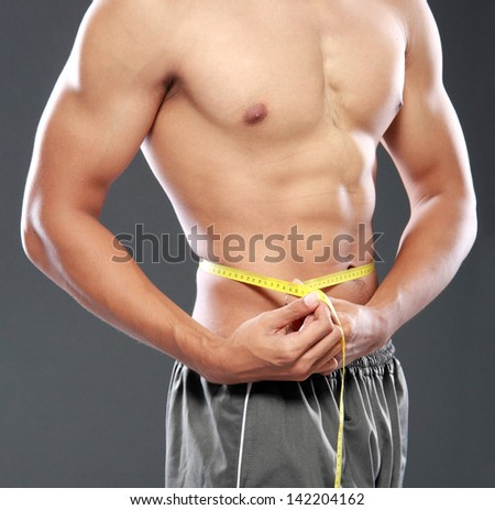 portrait of Men with perfect abs measuring his waist - stock photo