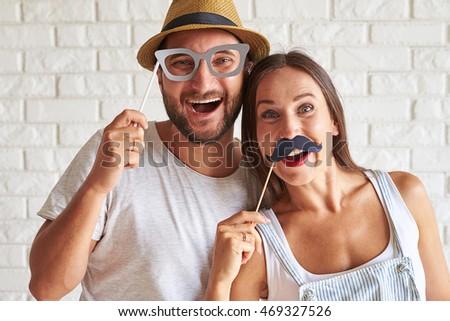 Portrait of merry couple holding paper moustache and glasses
