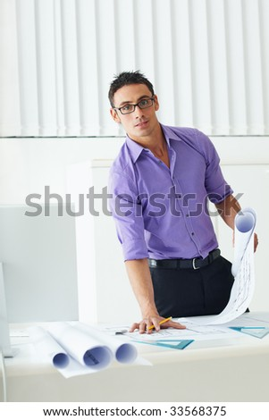 portrait of mid adult architect leaning on desk and looking at camera - stock photo