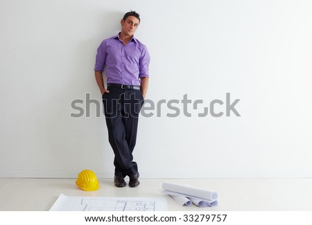 portrait of mid adult architect leaning on wall and looking at camera. Copy space - stock photo