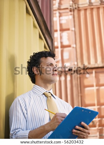 portrait of mid adult businessman leaning on cargo container and looking up. Vertical shape, side view, copy space - stock photo