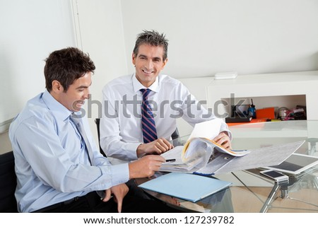Portrait of mid adult businessman with colleague discussing paperwork at a meeting in office - stock photo