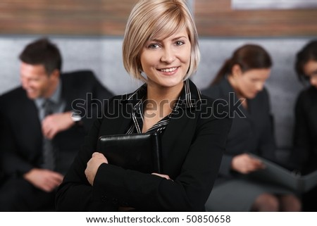 Portrait of mid-adult businesswoman looking at camera, smiling, business people in background. - stock photo