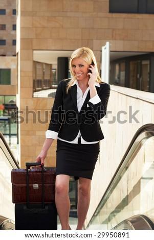 portrait of mid adult businesswoman on escalator, talking on the phone - stock photo