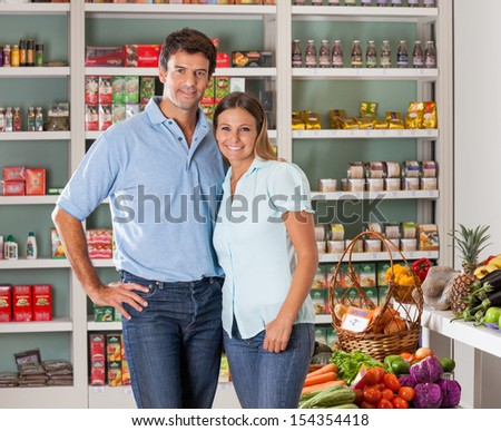 Portrait of mid adult couple standing in grocery store