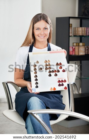 Portrait of mid adult female hairstylist with color catalog at beauty salon - stock photo