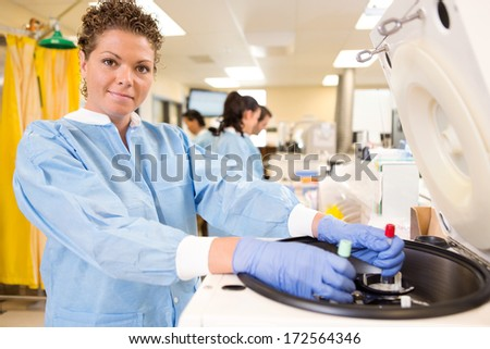 Portrait of mid adult female researcher loading test tubes in centrifuge