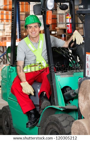 Portrait of mid adult forklift driver wearing safety helmet at warehouse - stock photo