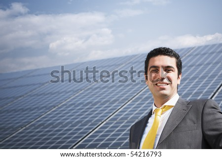 Portrait of mid adult italian businessman in solar power station, smiling at camera. Horizontal shape, front view. Copy space - stock photo