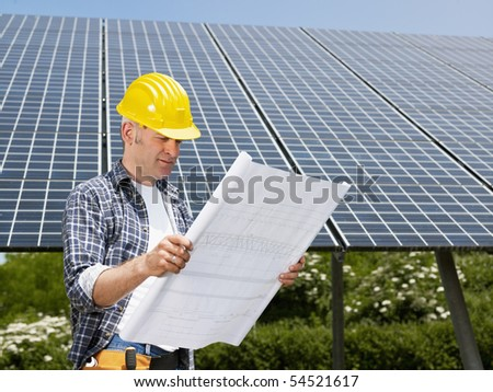 Portrait of mid adult italian male electrician reading blueprints in solar power station and smiling. Horizontal shape, side view. Copy space