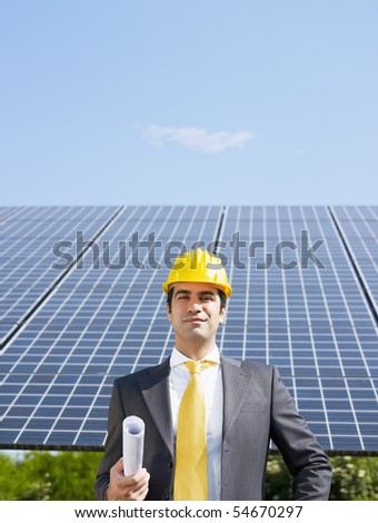 Portrait of mid adult italian male engineer holding blueprints in solar power station and smiling at camera. Vertical shape, front view. Copy space - stock photo