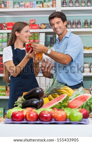 Portrait of mid adult male customer with saleswoman comparing bellpepper at supermarket