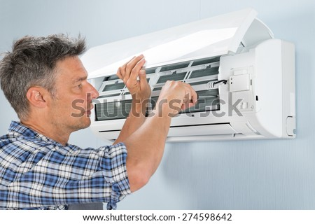 Portrait Of Mid-adult Male Technician Repairing Air Conditioner - stock photo