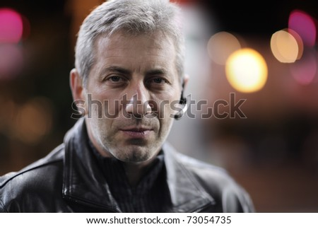 Portrait of mid-adult man in night city. Closeup, shallow DOF. - stock photo
