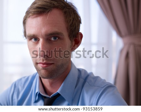 Portrait of mid adult pensive caucasian businessman in hotel room - stock photo