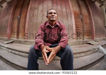 Portrait of mid adult poor asian man with hands joined, looking at camera. Fisheye shot - stock photo