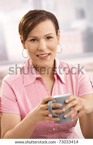 Portrait of mid-adult woman drinking coffee, looking at camera, smiling.? - stock photo